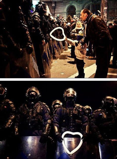 Child Handing Hart Shaped Balloon To Riot Police Officer